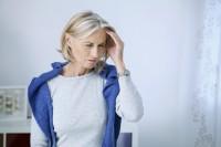 Frau, die unter einer der Kopfschmerzenarten leidet, hält sich den schmerzenden Kopf.