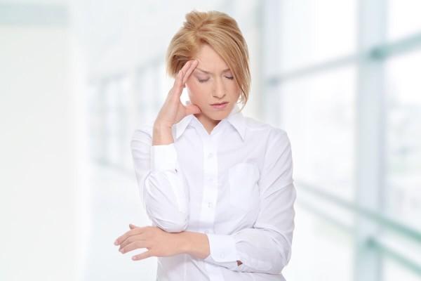 Frau hält sich den Kopf aufgrund von Clusterkopfschmerz