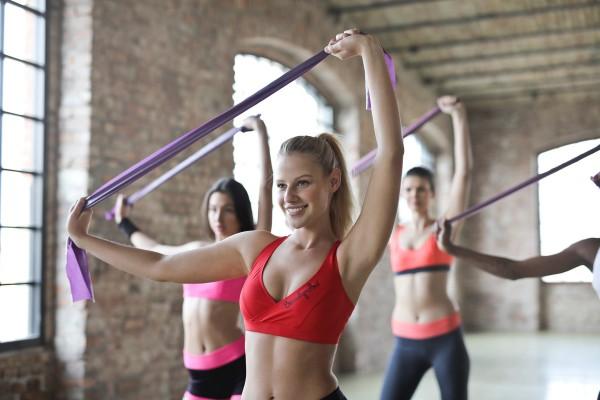 Frauen machen mit Terra-Band Sport im Gym