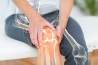 Mann mit Gelenkentzündung hält sich das schmerzende Knie.