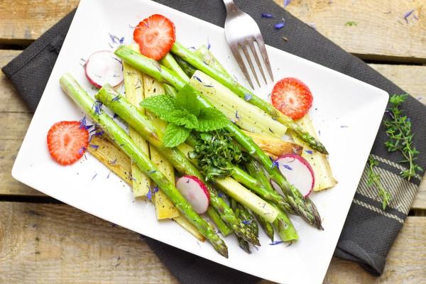Teller mit kohlenhydratarmen Lebensmittel - Spargel, Erdbeeren und Radieschen stehen auf einem Teller.