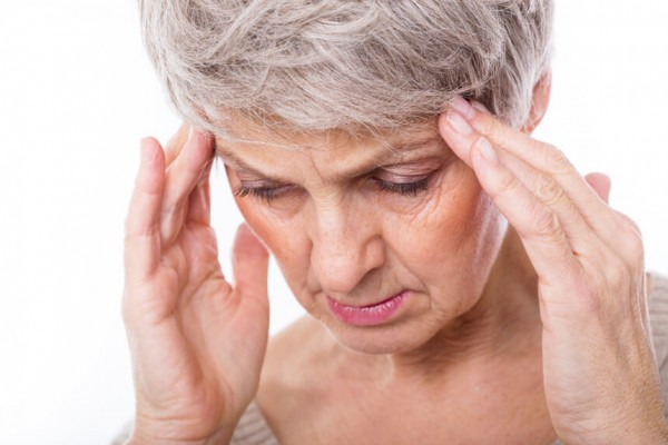 Frau hält sich den Kopf wegen Migräne