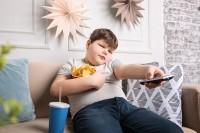 Kind mit Übergewicht sitzt mit Snacks vor dem Fernseher