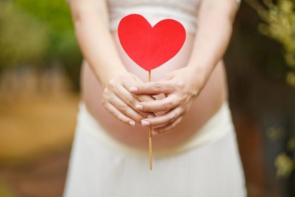 Pärchen hält Herz vor Bauch der schwangeren Mutter