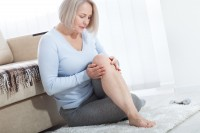 Frau hält sich ihr Knie wegen Gelenkschmerzen in den Wechseljahren