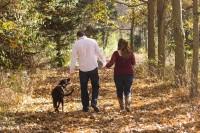 Pärchen geht mit Ihrem Hund im Wald spazieren.