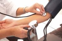 Doktor miest Blutdruck bei einer Patientin am Arm.