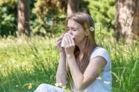Frau sitzt in der Wiese und ist aufgrund von Allergie am niesen.
