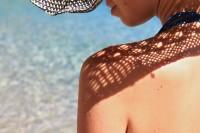 Frau sitzt am Strand am Meer und sonnt sich.