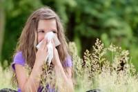 Kind steht mit Heuschnupfen auf der Wiese und putzt sich die Nase.