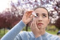 Frau verwendet Augentropfen gegen Heuschnupfen.