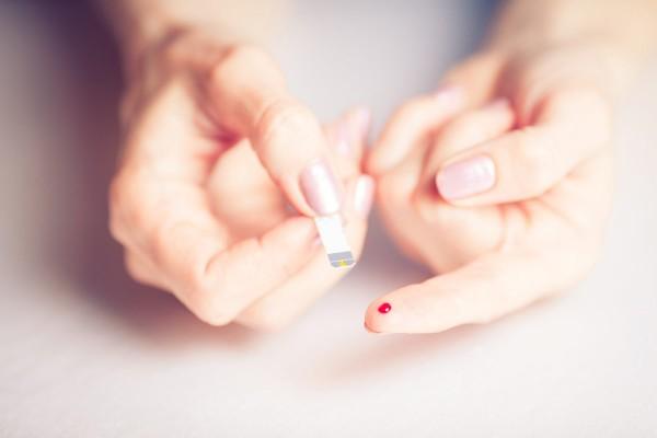 Frau nimmt sich Blut ab, um Diabetes zu erkennen bzw. zu behandeln