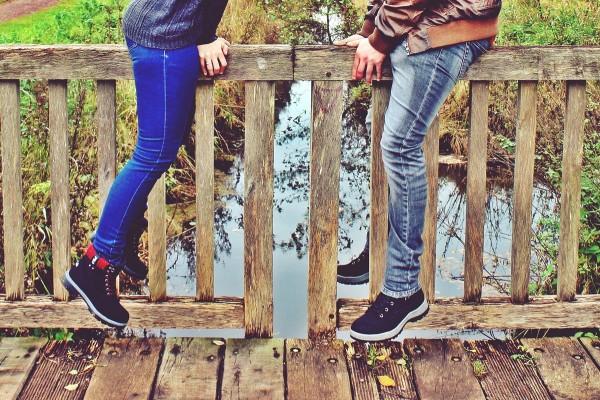 Pärchen sitzt auf dem Geländer einer Brücke.