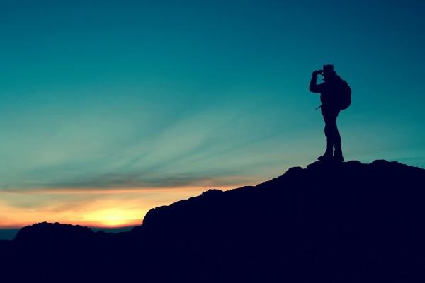 Mann steht auf einem Berg.