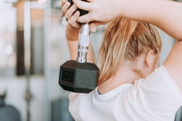 Frau macht im Fitnesstudio Hanteltraining um den Stoffwechsel anzukurbeln.