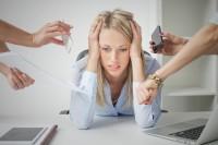 Frau sitzt auf der Arbeit und wird von Kollegen mit neuen Aufgaben bedrängt - bis hin zur völligen Erschöpfung.
