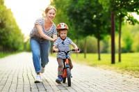 Frau, die Wert auf Bewegung und Gesundheit legt, unterstützt ihr Kind beim Fahrradfahren.