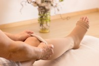 Frau zieht sich wegen Venenschwäche in den Beinen Kompressionstrümpfe an.
