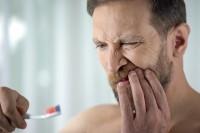Mann mit Zahnfleischentzündung hält sich beim Zähneputzen den Mund.