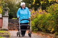 Frau mit Rollator, einem wichtigen Alltagshelfer für Senioren