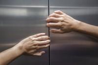 Hände versuchen eine Aufzugstür zu öffnen