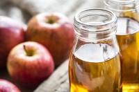 Flaschen mit Apfelessig und Äpfel auf einem Tisch