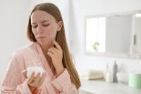 Frau mit Allergie im Gesicht begutachtet ihre Kosmetik im Badezimmer.
