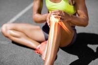 Frau mit Sportverletzung hält sich ihr schmerzendes Knie.