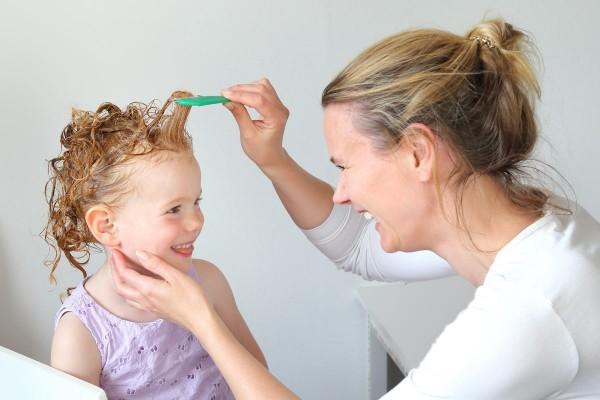 Mutter kämmt ihrem Kind mit dem Läusekamm die Haare.