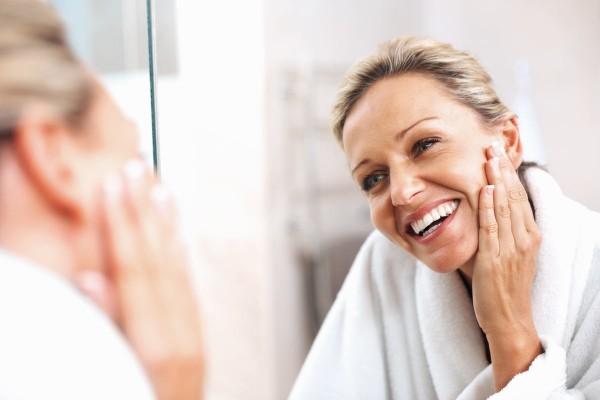 Frau schaut sich ihre Falten an Hals, Gesicht und Dekolleté im Spiegel an