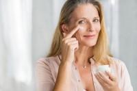 Frau trägt Pflege für reife Haut ab 50 auf ihr Gesicht auf.