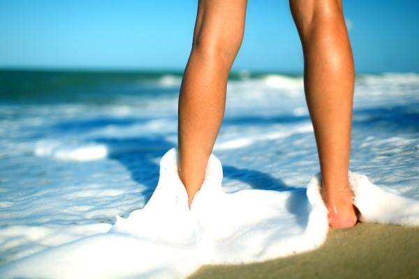 Fit wirkende Frau steht im Sommer knöcheltief im Meer