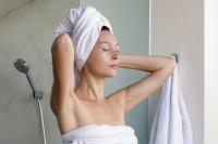 Frau bindet Handtücher um, nachdem sie mit Reiswasser ihre Haare gepflegt hat.