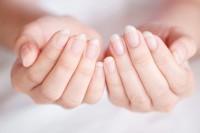 Frau betrachtet ihre Fingernägel, um sie auf Krankheiten zu untersuchen.