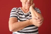 Frau mit Osteoporose hält sich den Ellbogen