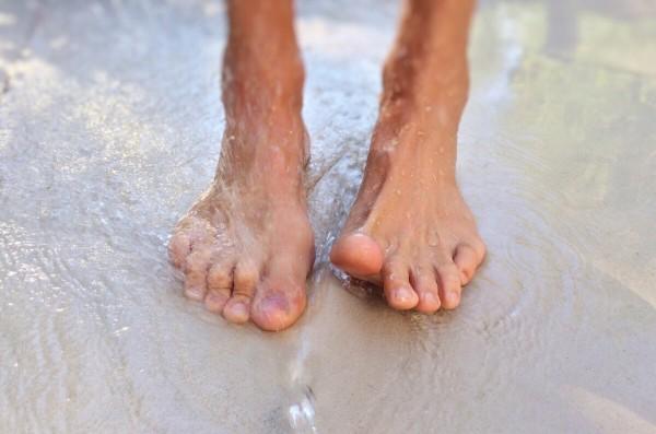 Nackte Füße am Strand am Meer.