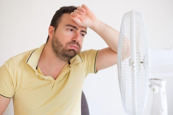 Mann steht schwitzend vor dem Ventilator und sucht Abkühlung.