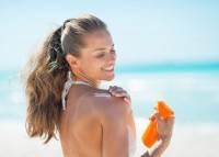 Frau am Strand cremt sich zum Schutz vor Mallorca Akne ein