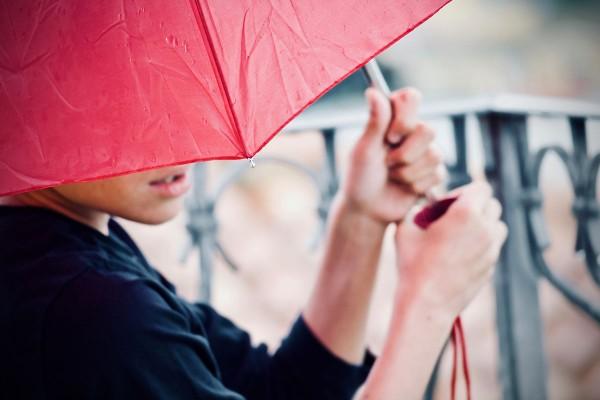 Frau mit Regenschirm sitzt draußen auf der Bank und wartet.