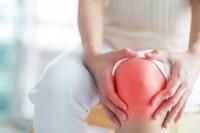 Frau hält sich durch Kniearthrose schmerzendes Knie.