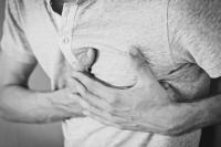 Man hält sich die schmerzende Brust.
