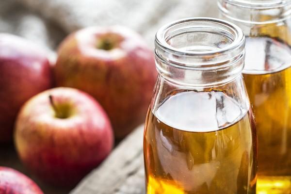 Glas Apfelessig mit Äpfeln daneben auf einem Tisch.