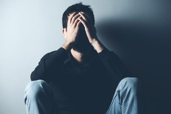 Mann mit Anzeichen von Depression hält sich auf dem Boden sitzend den Kopf