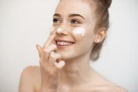 Frau verwendet Gesichtspflege für ihre empfindliche Haut.