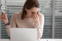 Frau sitzt wegen Vitamin B12 Mangel müde vor ihrem Laptop