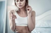 Frau mit Eisenmangelanämie hält ausgefallene Haare in der Hand.