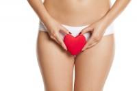 Frau hält als Symbol für Intimpflege ein Herz vor ihren Intimbereich