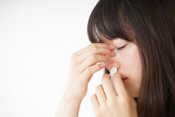 Frau hält sich ein Taschentuch an die Nase
