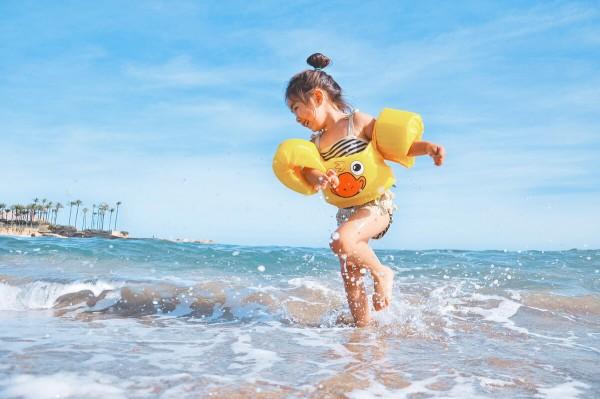 Kind spielt am Strand im Meer.