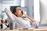 Frau, die ständig müde ist, gähnt am Arbeitsplatz.